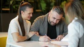 Взгляд со стороны риэлтора и молодых пар сидя на столе офиса обсуждая свойство для продажи Счастливые пары стали домом сток-видео