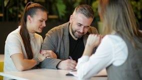 Взгляд со стороны риэлтора и молодых пар сидя на столе офиса обсуждая свойство для продажи Счастливые пары стали домом акции видеоматериалы
