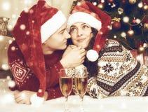 Счастливые пары с ложью шампанского около дерева и украшения xmas дома Зимний отдых и концепция влюбленности тонизированный желты Стоковые Изображения