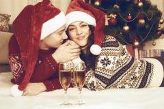 Счастливые пары с ложью шампанского около дерева и украшения xmas дома Зимний отдых и концепция влюбленности тонизированный желты Стоковое Изображение RF