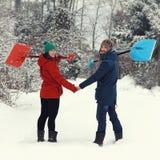 Счастливые пары с лопаткоулавливателями снега Стоковые Изображения