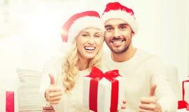 Счастливые пары с подарками и большими пальцами руки рождества вверх Стоковая Фотография