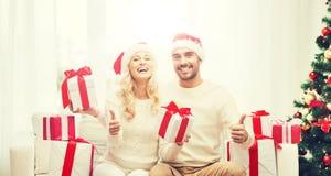 Счастливые пары с подарками и большими пальцами руки рождества вверх Стоковое Фото