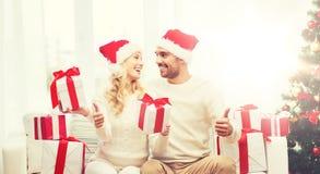 Счастливые пары с подарками и большими пальцами руки рождества вверх Стоковые Изображения