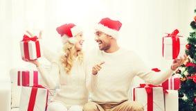 Счастливые пары с подарками и большими пальцами руки рождества вверх Стоковое фото RF