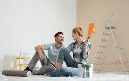 Счастливые пары с ремонтом краски планируя домашним стоковая фотография rf