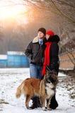 Счастливые пары с собаками в моментах леса зимы симпатичных внешних стоковые фотографии rf
