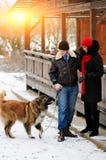 Счастливые пары с собаками в моментах леса зимы симпатичных внешних стоковое фото