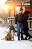 Счастливые пары с собаками в моментах леса зимы симпатичных внешних стоковое фото rf