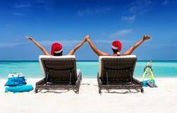 Счастливые пары с шляпами Санты на тропических каникулах Стоковые Фотографии RF