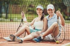 Счастливые пары теннисистов сидя с ракетками стоковая фотография