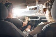 Счастливые пары управляя в автомобиле стоковая фотография