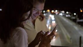 Счастливые пары усмехаясь в вечере на улице смотря смартфон совместно сток-видео