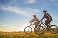 Счастливые пары mountainbike outdoors имеют потеху совместно на заходе солнца после полудня лета Стоковые Изображения RF