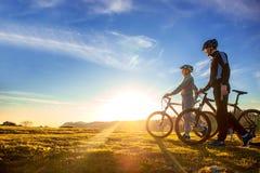 Счастливые пары mountainbike outdoors имеют потеху совместно на заходе солнца после полудня лета Стоковые Фотографии RF