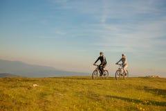 Счастливые пары mountainbike outdoors имеют потеху совместно на заходе солнца после полудня лета стоковое фото rf