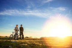 Счастливые пары mountainbike outdoors имеют потеху совместно на заходе солнца после полудня лета Стоковая Фотография RF