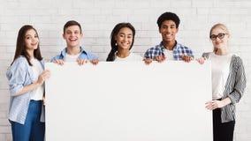 Счастливые подростки держа пустое знамя, белую кирпичную стену стоковое изображение rf