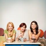 Счастливые подружки с кружками кофе Стоковые Изображения