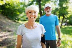 Счастливые подходящие старшие пары работая в парке стоковая фотография