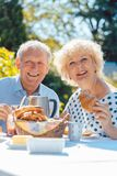 Счастливые пожилые пары есть завтрак в их саде outdoors стоковые фотографии rf