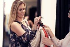 Счастливые покупки женщины для одежд в магазине стоковое изображение