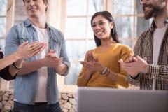 Счастливые положительные люди слушая к их коллеге стоковые фото