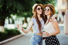 Счастливые положительные моменты 2 стильных девушек обнимая с коктейлями на улице в городе Attarctive портрета крупного плана сме стоковое фото rf