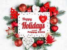 Счастливые праздники и счастливый текст 2019 с photoframe рождества окруженным ветвями дерева Нового Года, красными украшениями р стоковое фото