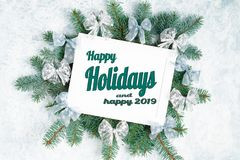Счастливые праздники и счастливый текст 2019 с photoframe рождества окруженным ветвями дерева Нового Года, серебряным рождеством стоковое фото
