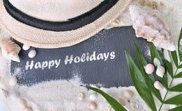 Счастливые праздники написанные на шифере в песке стоковое изображение