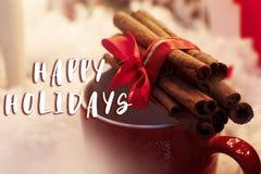 Счастливые праздники отправляют СМС знак на ручках циннамона с лентой на красном c стоковая фотография rf