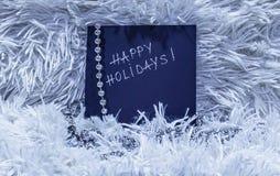 Счастливые праздники отправляют СМС на черной карточке с серебряными шариками на белом гриппе Стоковое Изображение RF