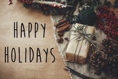 Счастливые праздники отправляют SMS знаку на стильной деревенской подарочной коробке рождества с ветвями ели, красными ягодами, к стоковые фото