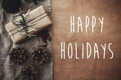 Счастливые праздники отправляют SMS знаку на стильной деревенской подарочной коробке с зелеными ветвями, анисовке, конусах сосны, стоковые фотографии rf