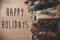 Счастливые праздники отправляют SMS знаку на стильной деревенской подарочной коробке рождества с ветвями ели, красными ягодами, к стоковое фото