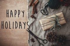 Счастливые праздники отправляют SMS знаку на стильной деревенской подарочной коробке с зелеными ветвями, анисовке, конусах сосны, стоковые изображения