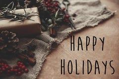 Счастливые праздники отправляют SMS знаку на стильной деревенской подарочной коробке рождества с ветвями ели, красными ягодами, к стоковое изображение rf