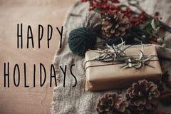 Счастливые праздники отправляют SMS знаку на стильной деревенской подарочной коробке рождества с ветвями ели, красными ягодами, к стоковое фото rf