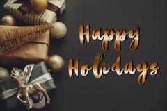 Счастливые праздники отправляют SMS, рукописный золотой знак на границе рождества стоковые изображения