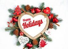Счастливые праздники отправляют SMS с ветвями праздника вечнозелеными, рамкой в форме сердца стоковые фотографии rf