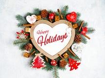 Счастливые праздники отправляют SMS с ветвями праздника вечнозелеными, рамкой в форме сердца стоковое изображение