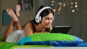 Счастливые предназначенные для подростков наблюдая средства массовой информации в таблетке на кровати дома видеоматериал