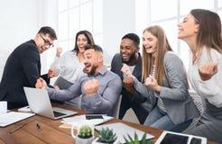 Счастливые предприниматели торжествуя с поднятыми кулаками в офисе стоковое фото