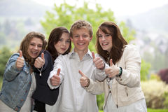 счастливые представляя большие пальцы руки подростков вверх Стоковая Фотография RF