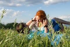 Счастливые привлекательные пары на одеяле пикника Соедините ослаблять совместно на летний день под облаками в голубом небе стоковые фотографии rf