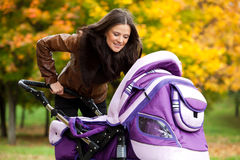 счастливые прогулки прогулочной коляски парка мамы Стоковые Изображения