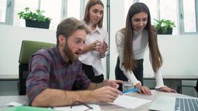Счастливые работники офиса радуются на темпах роста смотря экран ноутбука Коллеги имея потеху совместно Женщины сток-видео