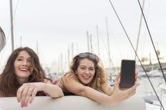 Счастливые радостные женские друзья усмехаясь и показывая передвижной дисплей Стоковые Изображения RF
