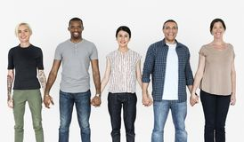 Счастливые разнообразные люди держа руки совместно стоковое фото